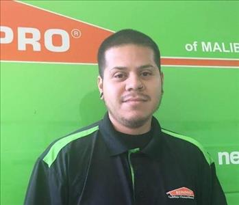 Male employee Jorge in front of the green van