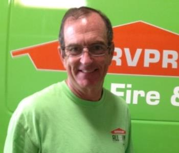 Male employee in front of green SERVPRO truck